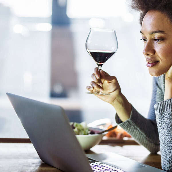 Young African American woman drinking wine while reading recipes over laptop in the kitchen.